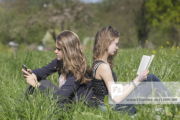 Teenage girls sitting in field  Freiburg im Breisgau  Baden-Württemberg  Germany
