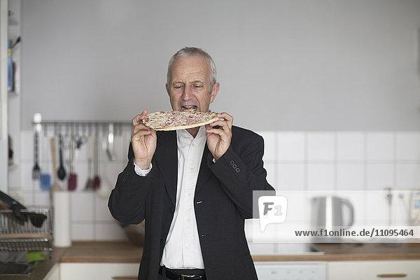 Senior businessman eating pizza in the kitchen  Freiburg im Breisgau  Baden-Württemberg  Germany