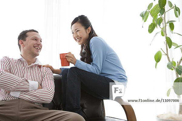 Young Couple Talking and Laughing on Sofa