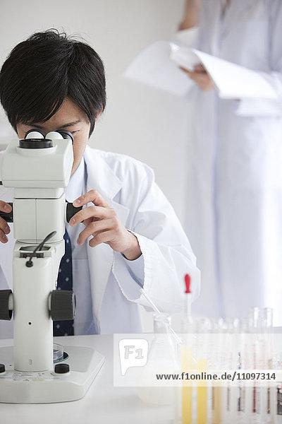 Young Male Scientist Using Microscope in Laboratory