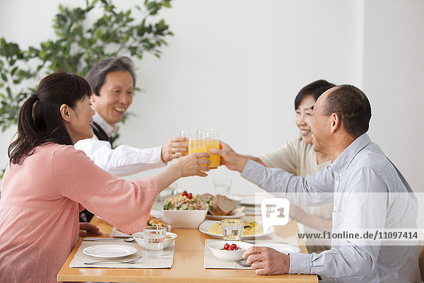 Four Mature People Toasting with Juice