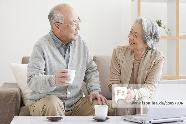 Senior Couple Using Laptop and Drinking Tea
