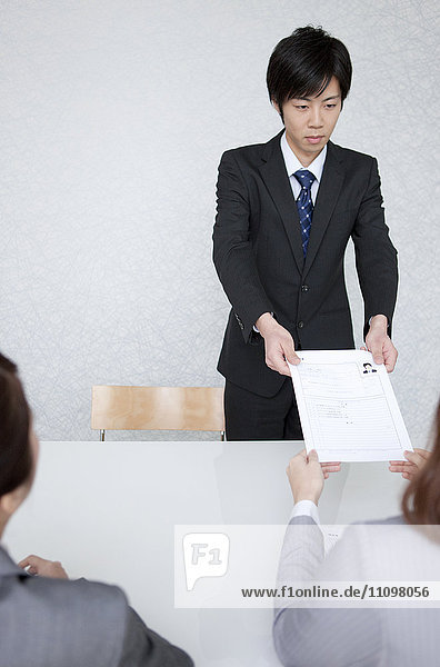 Young Man Giving His Resume To Business Women
