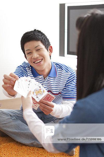 Teenage Girl and Boy Playing Cards