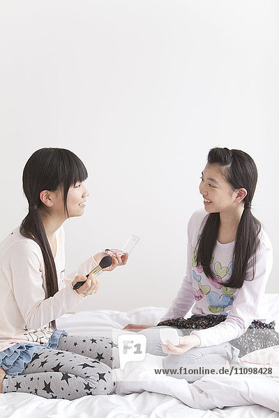 Two Teenage Girls Playing with Make Up