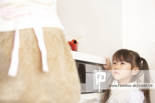 Girl watching mother cooking