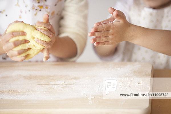 Girls kneading bread dough