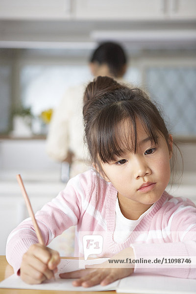 Girl doing homework at kitchen table