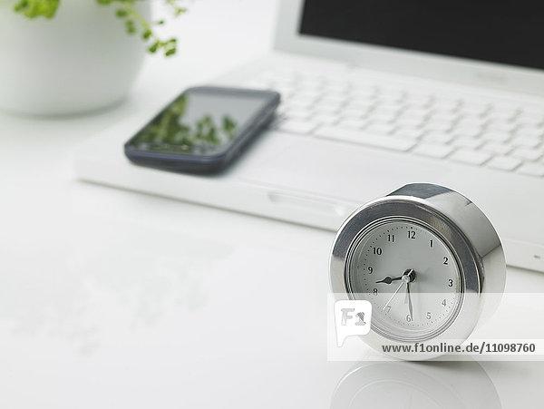 Laptop  smart phone and clock