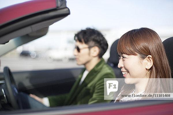 Couple in a convertible  Fukuoka Prefecture  Kyushu  Japan