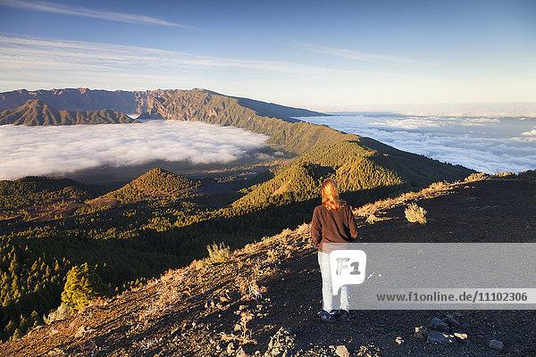 Woman on Birigoyo mountain looking at Cumbre Nueva and Cumbre Vieja at sunset  UNESCO Biosphere Reserve  La Palma  Canary Islands  Spain  Europe