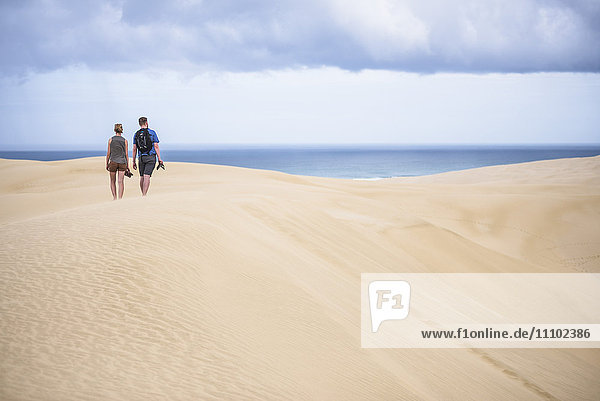 Two tourists at Te Paki Sand Dunes on 90 Mile Beach  Northland  New Zealand  Pacific