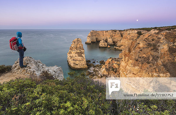 The photographer admires cliffs and ocean of Praia da Marinha at dawn  Caramujeira  Lagoa Municipality  Algarve  Portugal  Europe