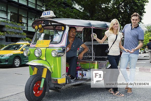 Tourists catching a Tuk-tuk near Khao San road in Bangkok  Thailand  Southeast Asia  Asia