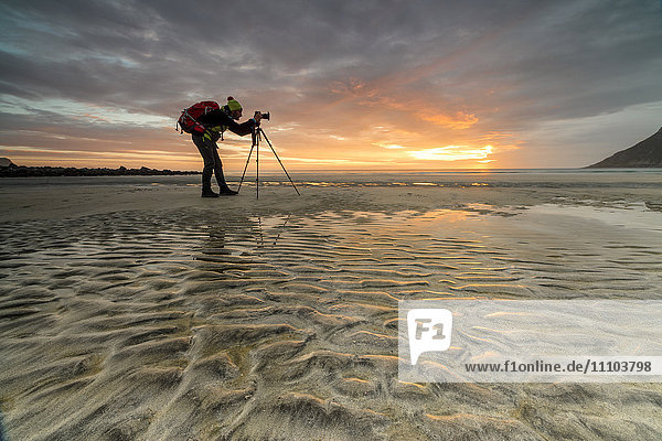 Midnight sun frames photographer in action on Skagsanden beach  Ramberg  Nordland county  Lofoten Islands  Arctic  Northern Norway  Scandinavia  Europe