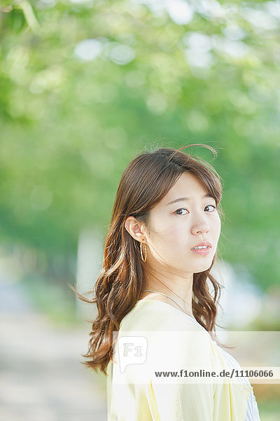 Attractive young Japanese woman in a city park