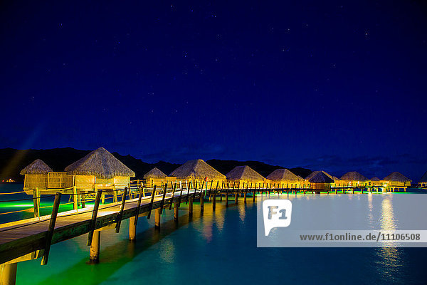 Overwater bungalows at night  Le Taha'a Resort  Tahiti  French Polynesia  South Pacific  Pacific