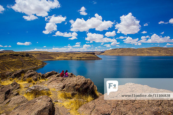 Two people sitting on the edge of Lake Titicaca  Peru  South America