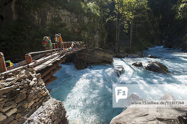 Hikers crossing a wooden bridge between Chhepka and Amchi Hospital in Dolpa  a remote region of Nepal  Himalayas  Nepal  Asia