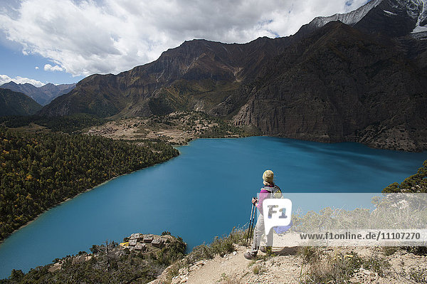 A trekker stands above the turquoise blue Phoksundo Lake in the Dolpa region  Himalayas  Nepal  Asia