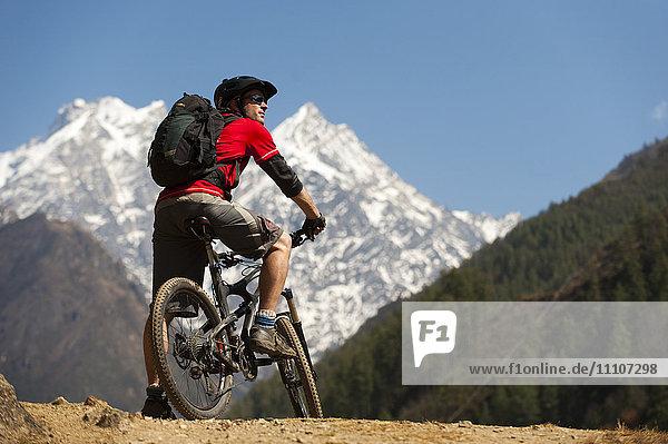 A mountain biker in the Tsum Valley looks at Ganesh Himal mountains  Manaslu region  Himalayas  Nepal  Asia