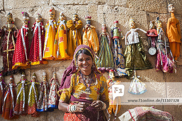 A woman sells puppets along the fort walls in Jaisalmer in the desert state of Rajasthan  India  Asia