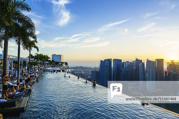 Infinity pool on the roof of the Marina Bay Sands Hotel with spectacular views over the Singapore skyline at sunset  Singapore  Southeast Asia  Asia