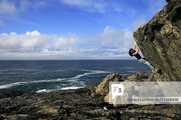 A climber bouldering by the sea near St. Ives  Cornwall  England  United Kingdom  Europe