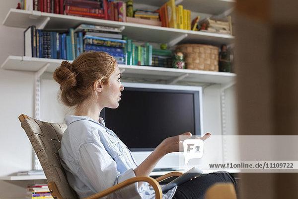 Seitenansicht der Frau beim Sitzen auf dem Stuhl zu Hause