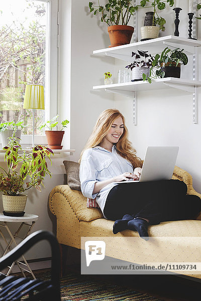 Smiling woman using laptop while resting on chaise longue at home