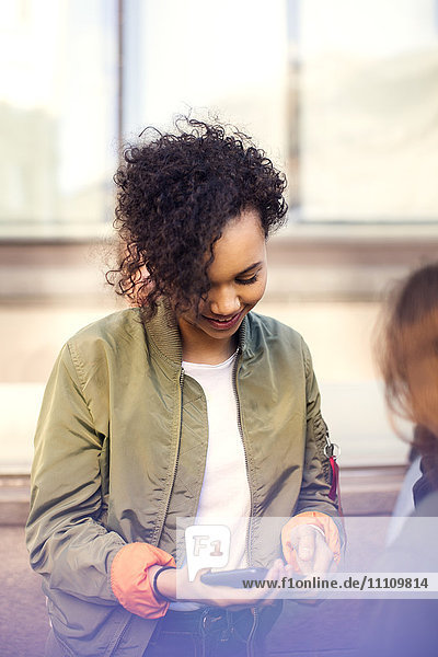 Smiling teenager with curly hair using smart phone while standing against building