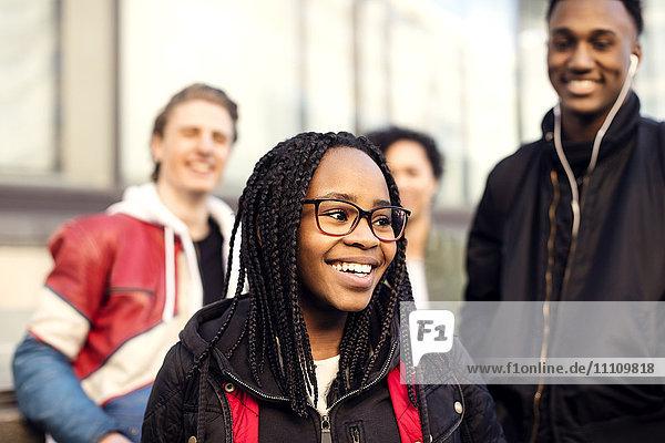Lächelnder Teenager mit geflochtenem Haar  der eine Brille trägt und gegen Freunde in der Stadt steht.