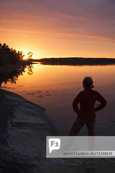 Rückansicht der Frau  die bei Sonnenuntergang auf dem See gegen den Himmel steht.