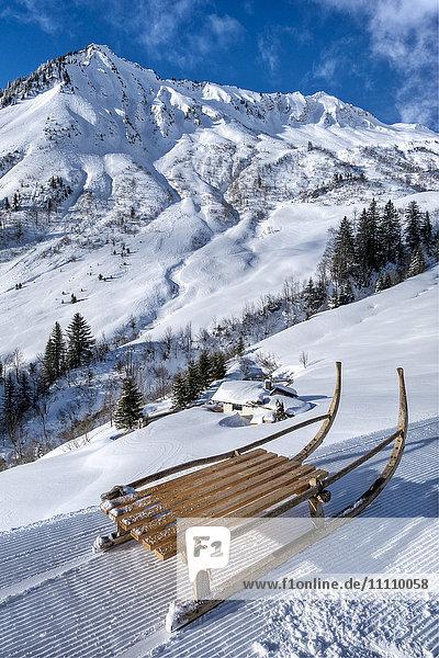 Austria  Biosphere Park Grosses Walsertal Bregenzerwald Mountains  mountain hut and Türtschhorn (2069 m) peak from Faschina Pass  sledge