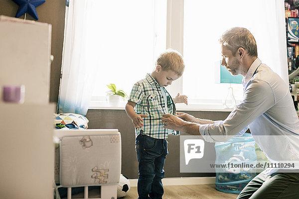 Vater verkleidet den Sohn in einem hell erleuchteten Zimmer zu Hause an einem sonnigen Tag.