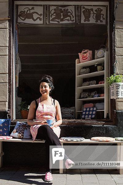 Fröhlicher Besitzer beim Kaffeetrinken auf dem Tisch bei Kissen außerhalb des Stoffladens