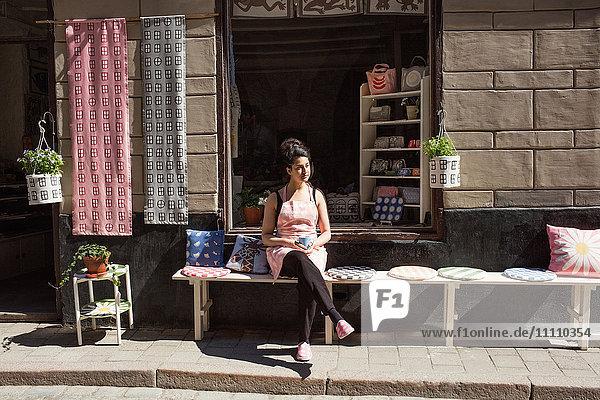 Nachdenklicher Besitzer beim Kaffeetrinken auf dem Tisch bei Kissen außerhalb des Stoffladens