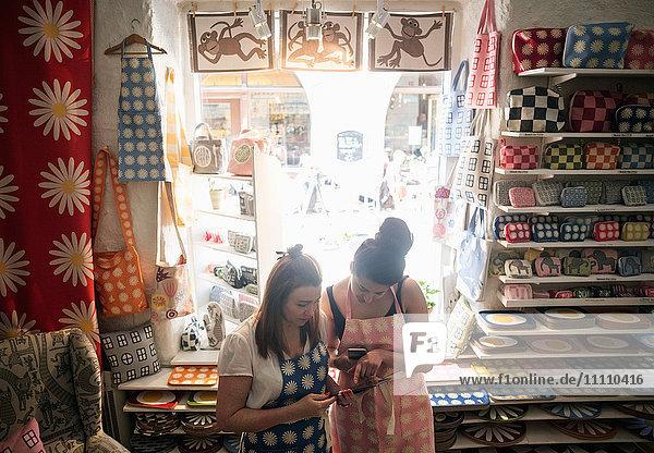 Hochauflösende Ansicht von Besitzern  die während der Nutzung von Smartphones und digitalen Tabletts im Geschäft diskutieren.