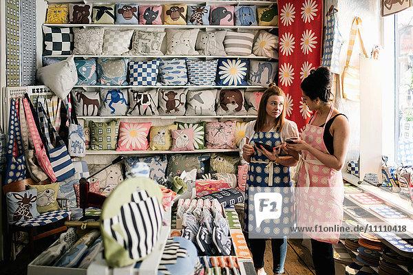 Besitzerinnen im Gespräch mit Smartphone und digitalem Tablett im Stoffladen