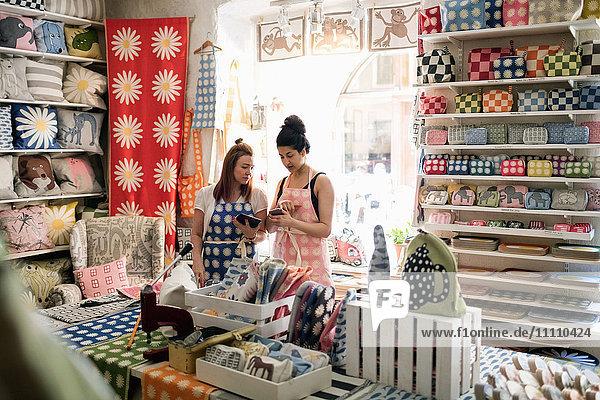 Besitzerinnen von Smartphones und digitalen Tabletts im Stoffladen