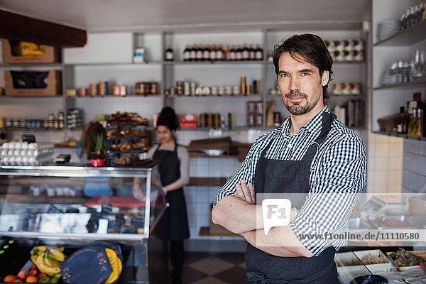 Porträt eines selbstbewussten Besitzers mit gekreuzten Armen gegen einen Kollegen im Geschäft