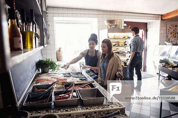Inhaberin hilft dem Kunden im Geschäft