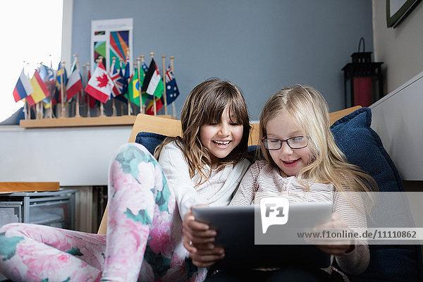 Lächelnde Freunde  die in der Schule auf dem Sofa liegen und ein digitales Tablett benutzen.