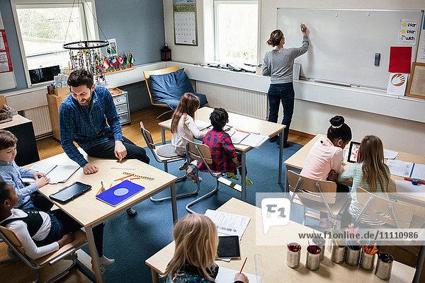 Hochwinkelansicht der Lehrerin beim Schreiben an Bord  während der Lehrer mit den Schülern am Schreibtisch im Klassenzimmer sitzt.