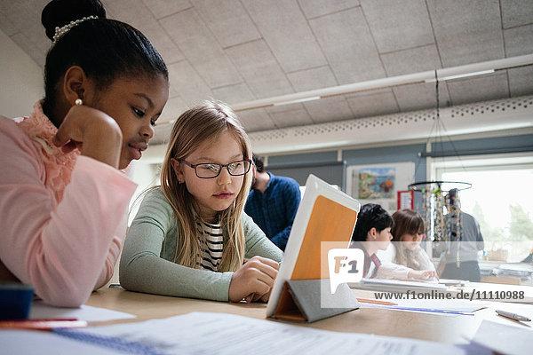 Schülerinnen lesen digitales Tablett am Schreibtisch im Klassenzimmer