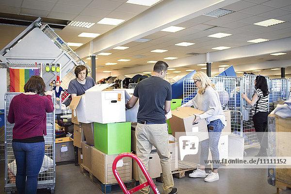 Freiwillige  die während der Arbeit in der Werkstatt Kartons anordnen