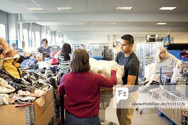 Mann  der Frau beim Halten von Plastik unterstützt  während Freiwillige in der Werkstatt arbeiten.