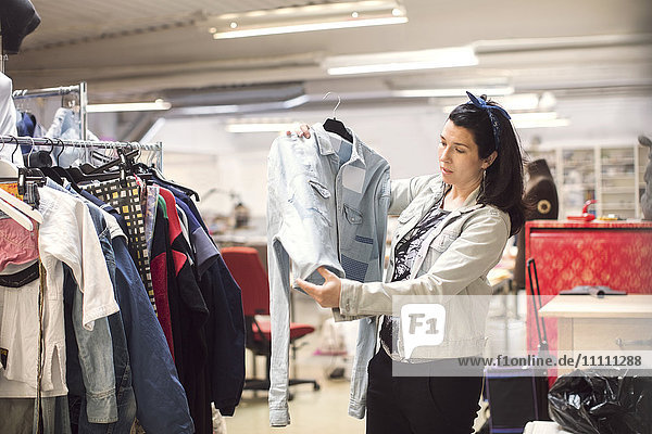 Seriöse Freiwillige bei der Suche nach einer Jacke mit Kleiderständer in der Werkstatt