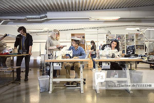 Freiwillige  die mit Menschen diskutieren  während Freiwillige in der Werkstatt arbeiten
