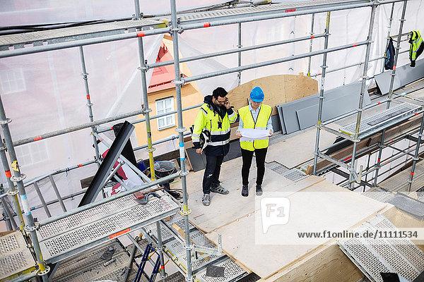 Hochwinkelansicht der Mitarbeiterin beim Lesen von Dokumenten während des Telefonats auf der Baustelle